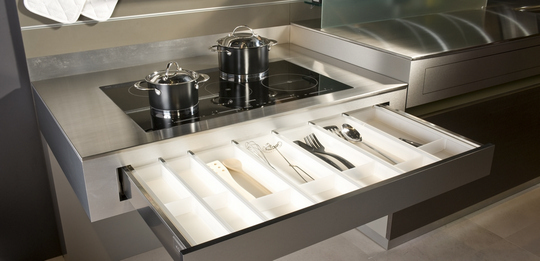 The worktop can be moved to any height at the push of a button, and the handle-less drawer with push function is directly accessible below this.